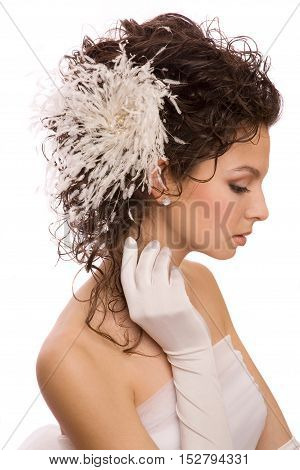 Profile of young beautiful modern bride with feather hairpin in her hair and her hand in the glove near face isolated on the white background