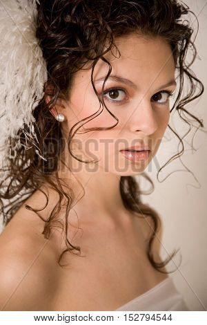 Close-up of young beautiful bride with feather hairpin in her hair