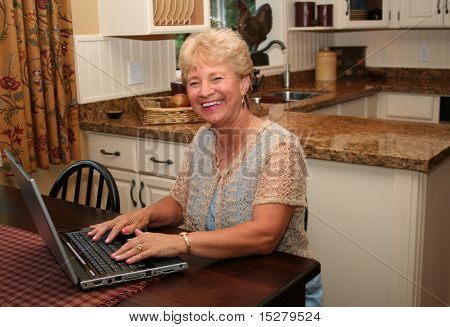 Grand-ma in the kitchen using her laptop.
