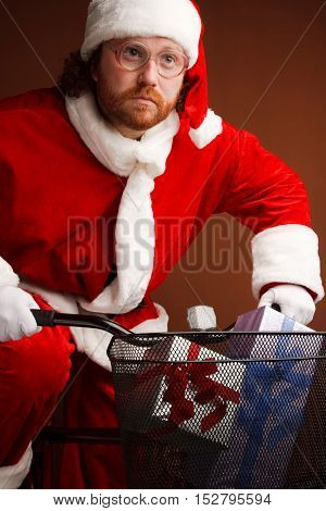 Odd purposeful man dressed in Santas costumeis cycling with presents