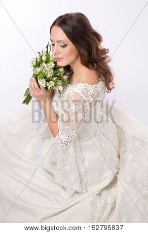 Bride dressed hippie style is sitting with flowers in her hands