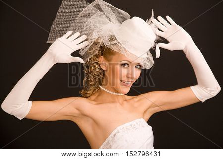 Joyfull bride dressed in retro style with her arms raisedon the black background