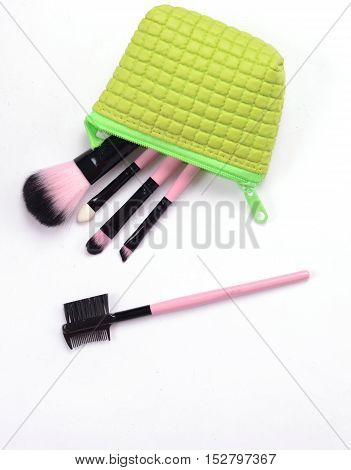 Woman Cosmetics stuff in green bag isolated on white background.