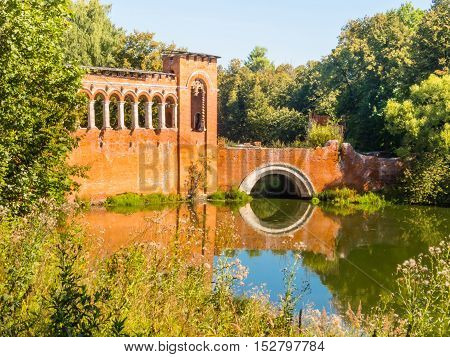 Destroyed Gothic bridge with loopholes. Old pond in the Russian manor of the 18th century