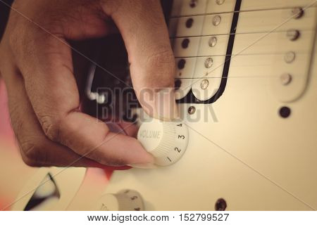 Hand of guitar player on tone control.