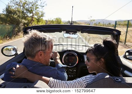 Couple driving in open top car look at each other, back view