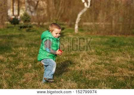 Boy plays with a ball in the autumn park. Family time. The happiness of childhood. Outdoor Activities.