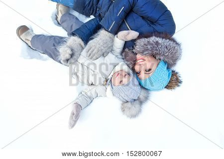 Mother and little daughter lay on the snow in winter park. Happy family. Childhood and parenthood happiness.
