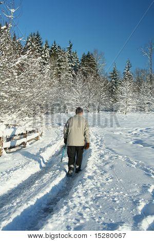 Elderly gentleman walking alone through a snow covered park.