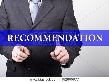 recommendation written on virtual screen. technology, internet and networking concept. man in a business suit and tie holds a PC tablet.