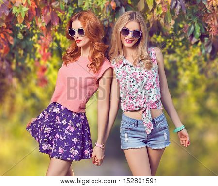 Fall Fashion. Urban Model Woman in Fashion Outfit Having Fun. Glamour Sexy Hipster Girl, fashion Trendy Hairstyle. Sisters Friends Smiling Enjoy Autumn Nature, Stylish Sunglasses. Autumn Outdoor Park