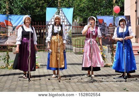 Grodno, Belarus - June 4, 2016: 11 Festival of National Cultures in Grodno, Belarus. Four women in the German national costumes singing in the street scene.