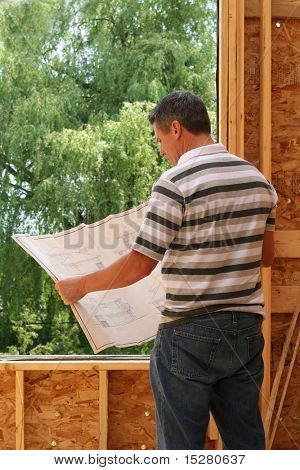 Man looking at the blue prints of his new home still under construction.