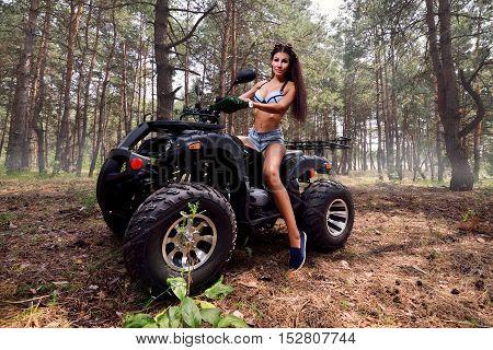 Sexy wonan on atv quad bike riding forest