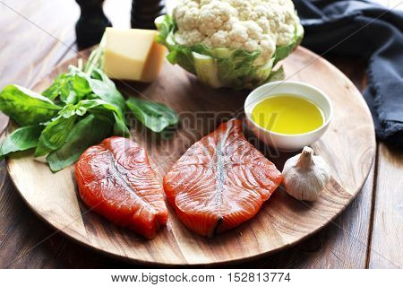 Raw humpback salmon steaks, rustic wooden background, above view. Fillet with fresh ingredients for tasty cooking and frying pan.  Top view. Healthy and diet food concept.