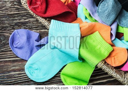 scattered multi-colored socks and laundry basket on a wooden background