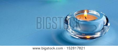 A small candle in a round glass candleholder. Blue background. Place for text. The Christmas cheer.