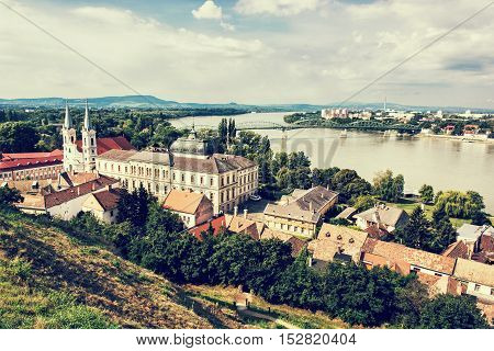 View from Esztergom basilica. Saint Ignatius church and Maria Valeria bridge Hungary. Travel destination. Cultural heritage. Retro photo filter. Religious architecture. Danube river.