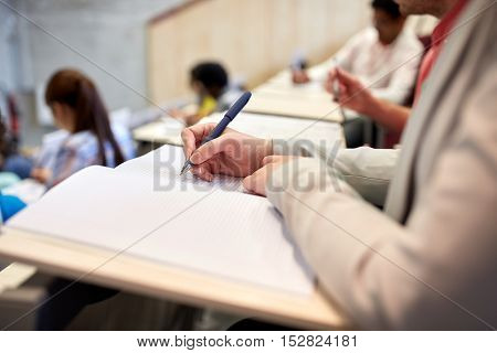 education, high school, university, learning and people concept - student writing to notebook at exam or lecture