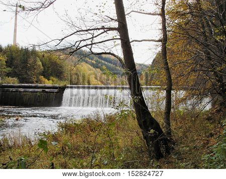 The Zschopau Valley in Erzgebirge in fall, weir at the Zschopau River in Saxony, Germany; colorful trees
