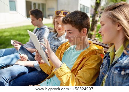 technology, internet and people concept - group of happy teenage friends or students with tablet pc computer outdoors
