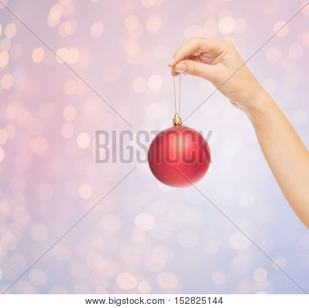 christmas, decoration, holidays and people concept - close up of woman hand holding christmas ball over rose quartz and serenity lights background