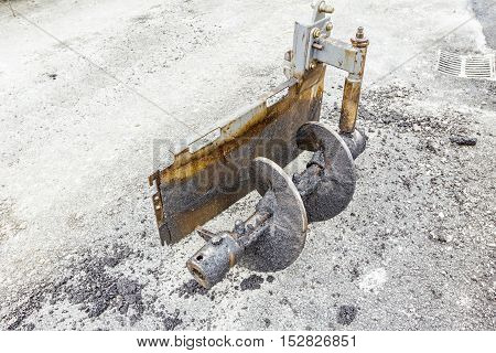 Dirty metal auger on shaft is dismantled from asphalting machine. Asphalt spreader out of order