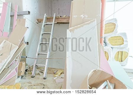 Crushed segments of gypsum drywall are dropped in pile at building site. poster