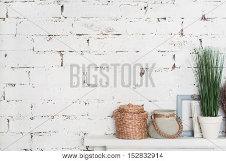 White on white. Wooden white shelf decorated with flowerpots and picture frames against brick wall.