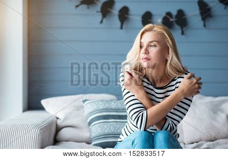 Hiding emotions. Pretty-looking blond lady sitting with crosses arms on couch , full of pillows against blue wall with decorative birds.