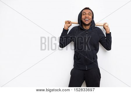 Laughing African American man with baseball bat is standing against white background. Concept of enjoying sports. Mock up