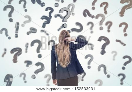 Woman scratching her head and standing in a room full of floating question marks. Concept of questions and answers. Toned image