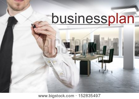 businessman in modern office writing businessplan in the air