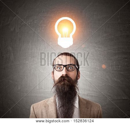Baffled man in glasses with long beard is standing against blackboard with glowing light bulb sketch. Concept of bright idea