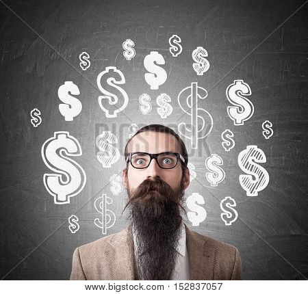 Baffled man wearing glasses and long beard is standing near blackboard with dollar signs on it and looking into your soul
