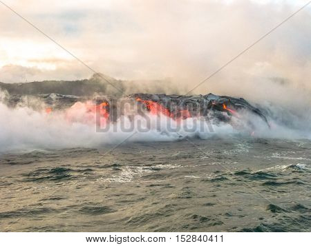 Scenic view from boat in the sunrise of Kilauea Volcano in Hawaii Volcanoes National Park, while erupting lava into Pacific Ocean, Big Island, Hawaii.