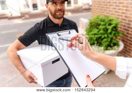 hand of a female customer signing for delivery on a clipboard