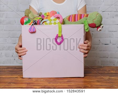 Woman with box of toys ready for donation