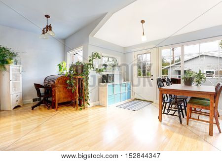 Bright entrance room in craftsman style house. Light tones hardwood floor View of dining area and small home office . Northwest USA