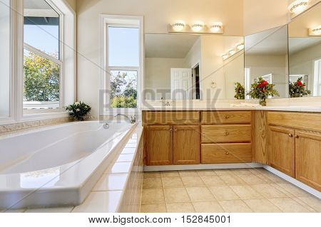 Luxury Bathroom Interior With Wooden Cabinets And White Bathtub