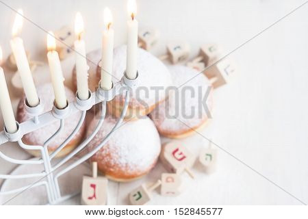 Jewish traditional holiday Hannukah with menorah doughnuts and dreidles. Copy paste background.