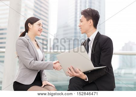 businesswoman shaking hands with businessman in office in hongkong