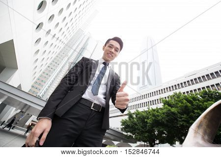 businessman smile to you and thumb up in honkong asian