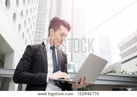 businessman concentrates using computer in honkong asian