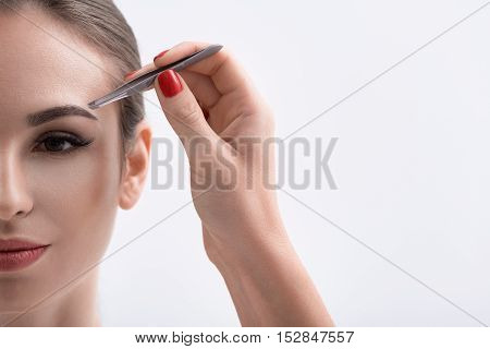 Close up of cosmetician hand pulling out female eyebrows by tweezers. Young woman is looking forward with confidence. Isolated and copy space in right side