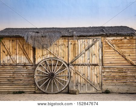 wheel of an old chariot against the gate of a warehouse made of wood and a thatched roof