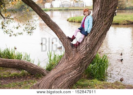 Little ginger girl in an earmuffs standing on the tree in the park against the lake with the ducks
