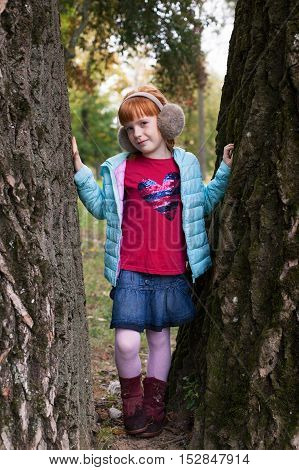 Little ginger girl in an earmuffs standing between the trees in the park
