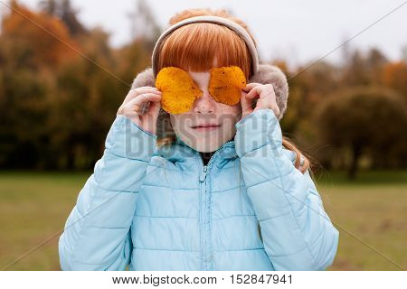 Little ginger girl in an earmuffs holding yellow leaves at the eyes
