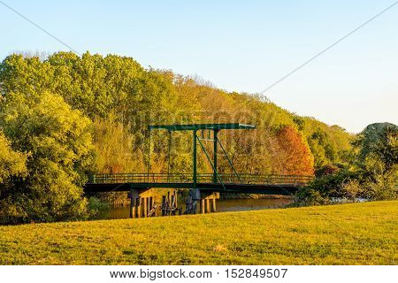 Historic drawbridge from 1939 built across a creek in a Dutch nature reserve. It is a sunny day in the fall season.